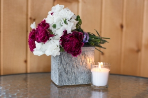 A bouquet of flowers sits on top of a slate box, which holds the ashes of a baby boy named Amos. A lit white votive candle sits in front of the box.